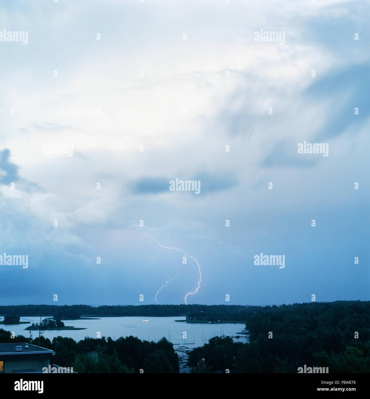 Finland, Helsinki, Roihuvuori, Stromsinlahti, Double lightning striking on horizon - Stock Image