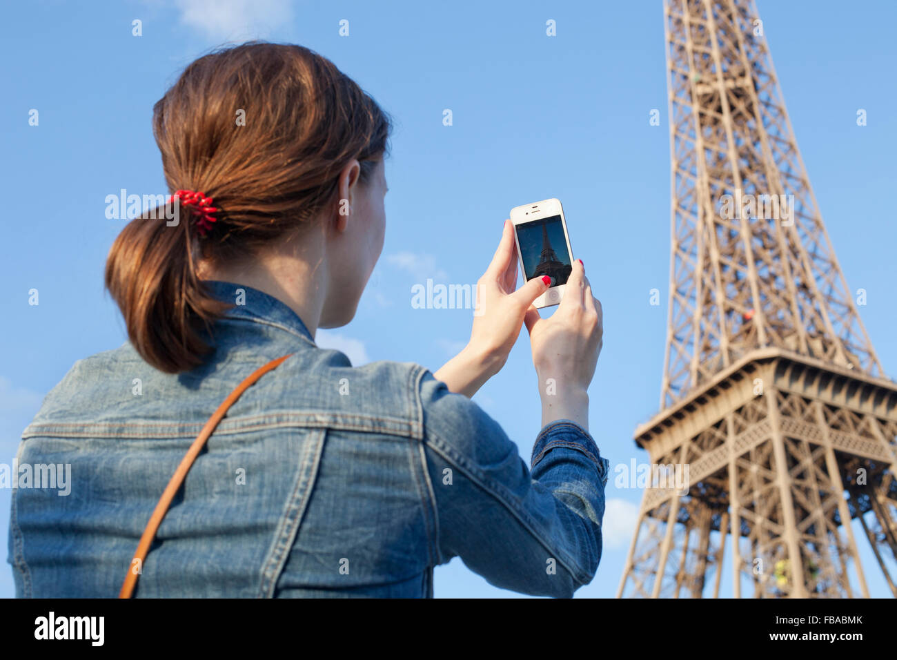 France, Ile-de-France, Paris, Rear view of woman taking picture of Eiffel Tower Stock Photo