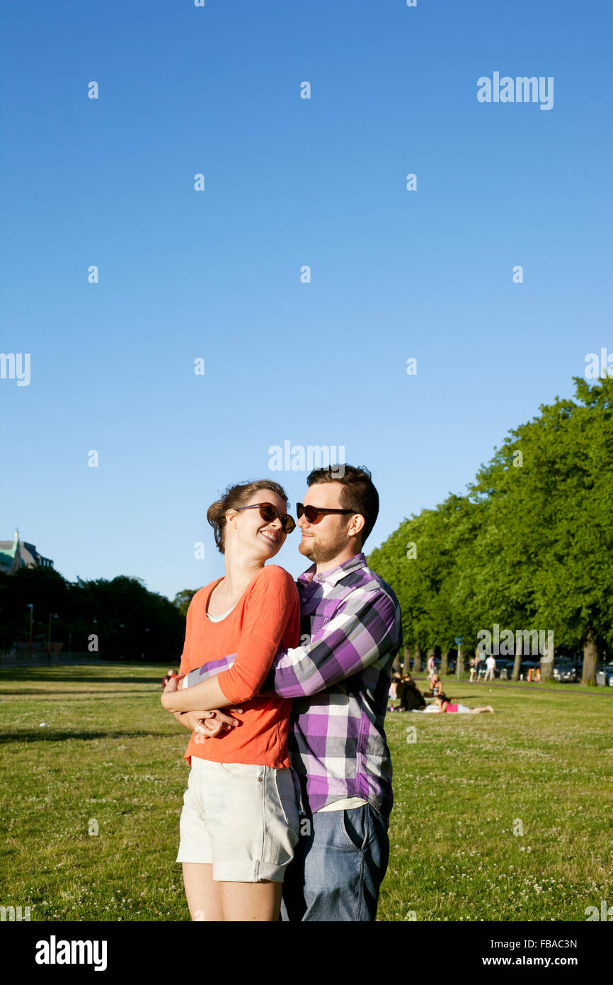 Finland, Uusimaa, Helsinki, Kaivopuisto, Young couple embracing in park - Stock Image