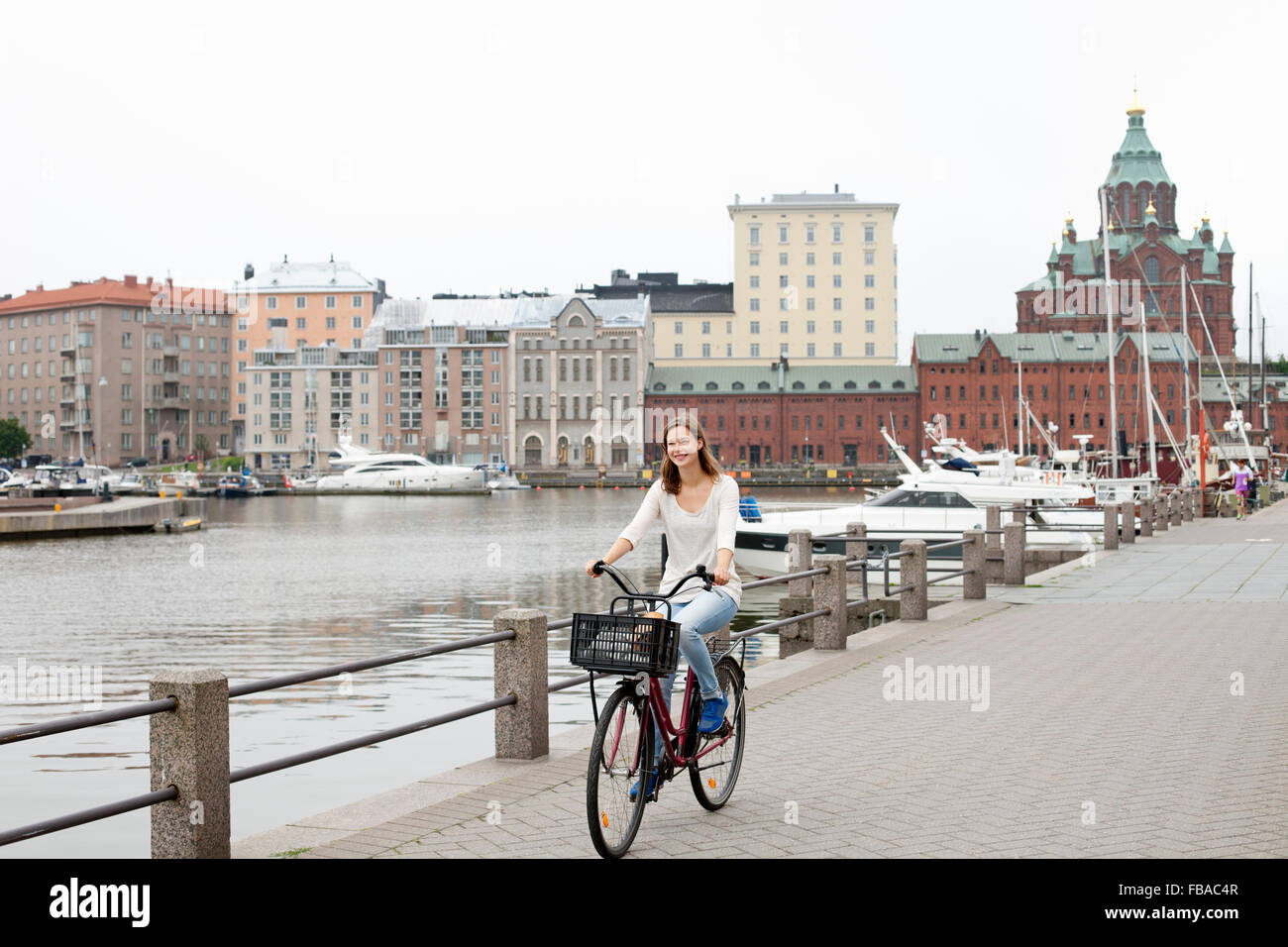 Finland, Uusimaa, Helsinki, Kruunuhaka, Young woman riding bicycle in city Stock Photo