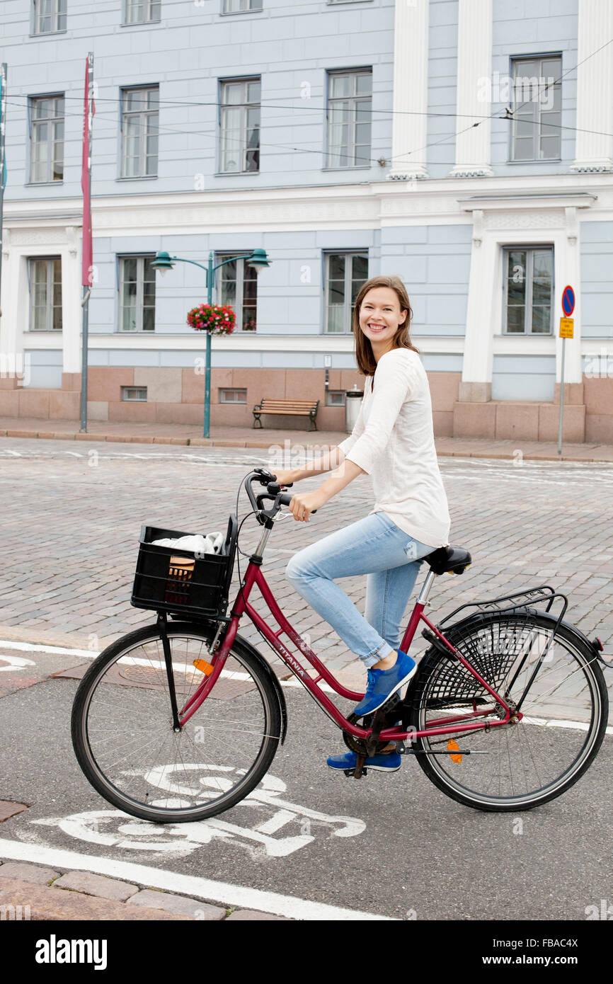 Finland, Uusimaa, Helsinki, Kruunuhaka, Young woman riding bicycle in city Stock Photo