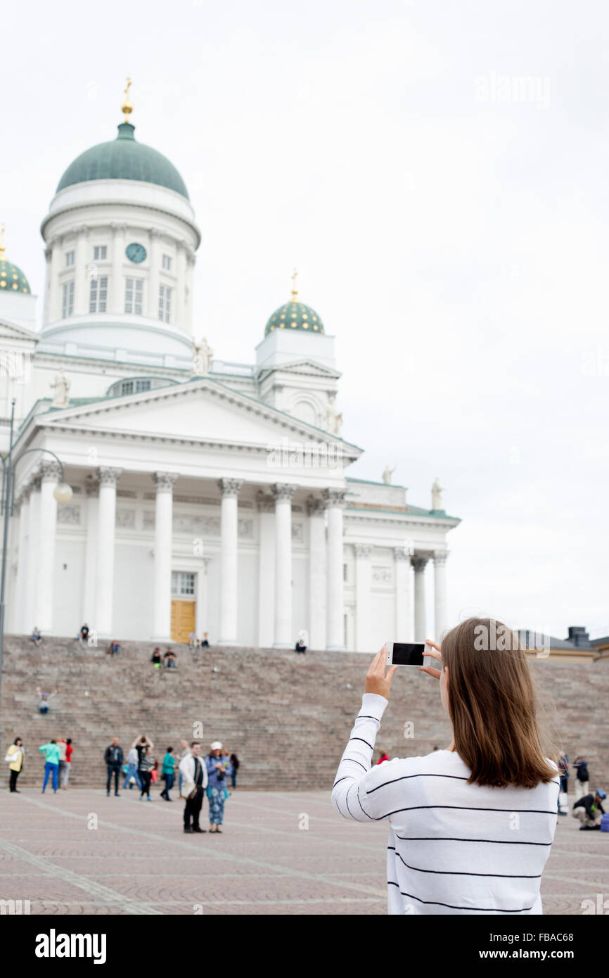 Finland, Uusimaa, Helsinki, Senaatintori, Young woman photographing Lutheran Cathedral Stock Photo