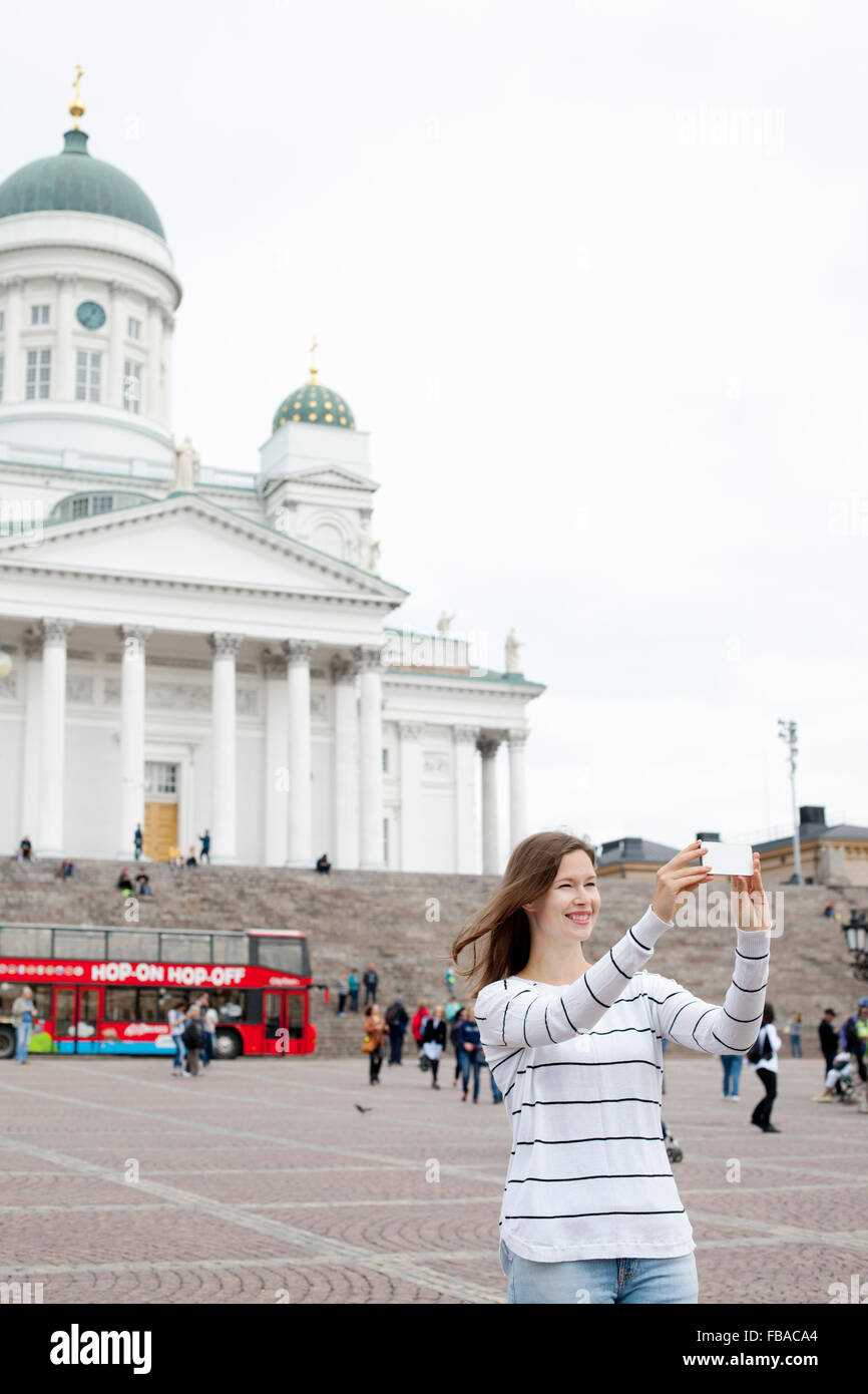Finland, Uusimaa, Helsinki, Senaatintori, Young woman photographing self with Lutheran Cathedral in background Stock Photo