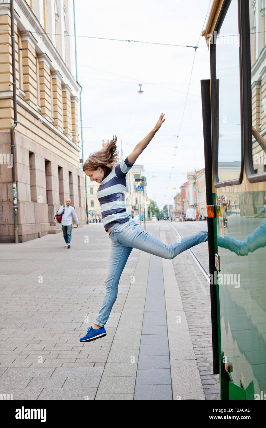 Finland, Uusimaa, Helsinki, Kruunuhaka, Young woman jumping out of tram Stock Photo