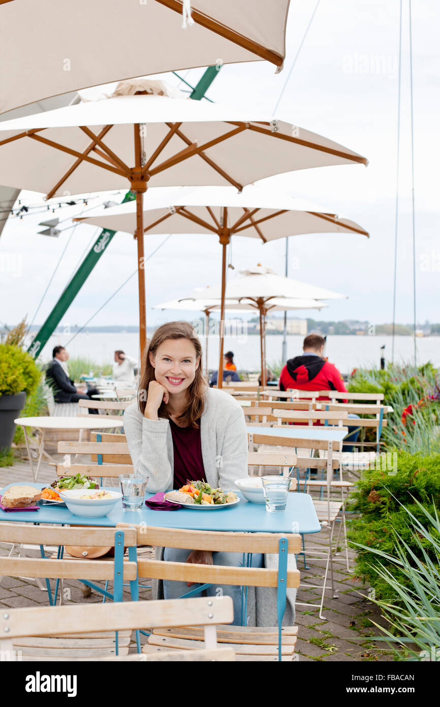 Finland, Uusimaa, Helsinki, Kaivopuisto, Portrait of smiling young woman in open air restaurant - Stock Image