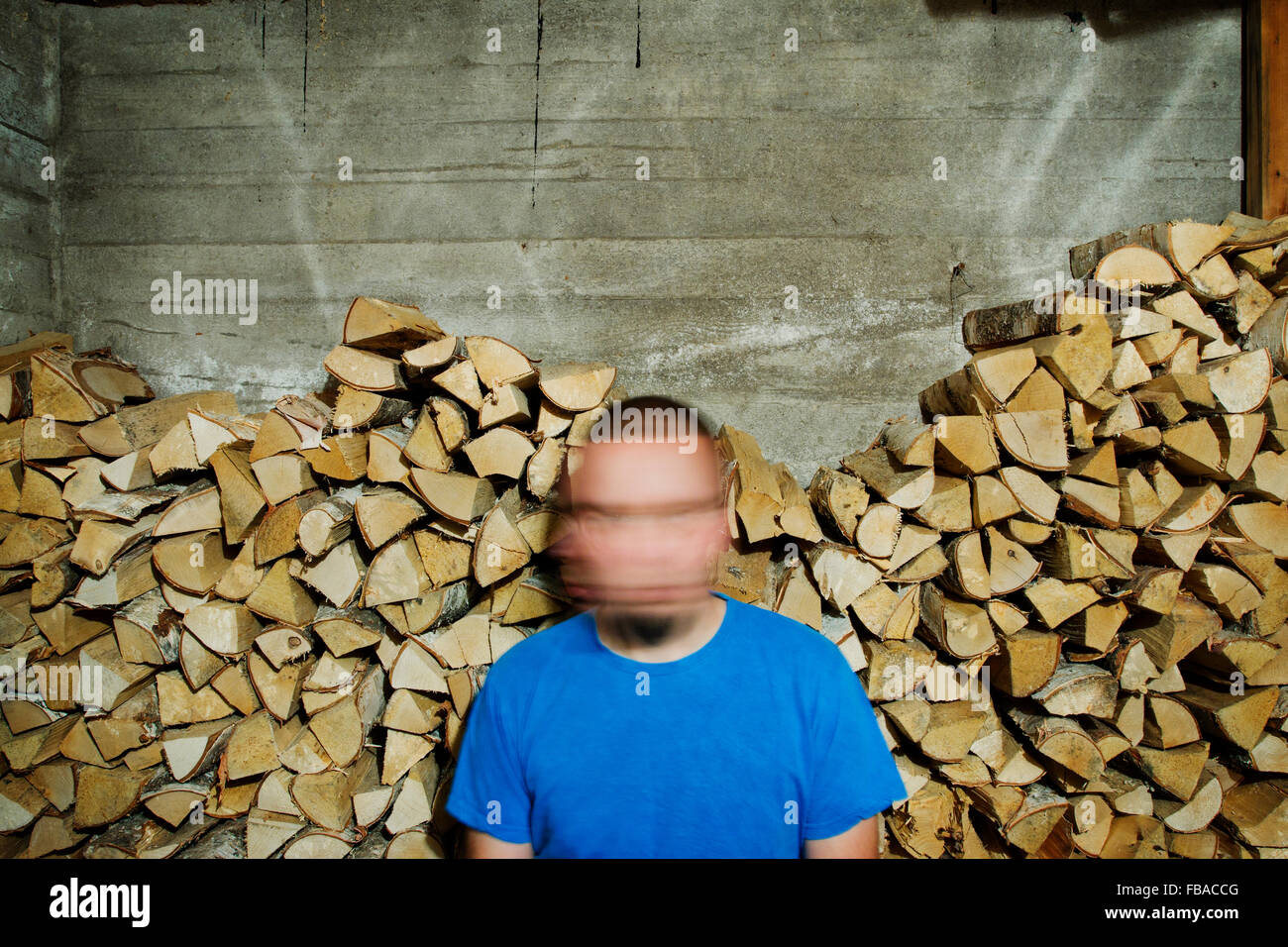 Finland, Heinola, Man with blurred face against pile of wood - Stock Image
