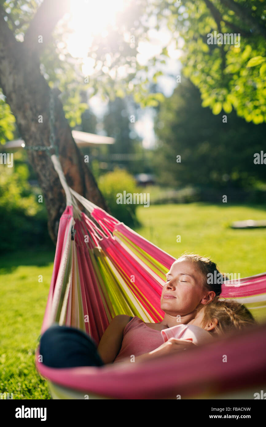 Finland, Heinola, Paijat-Hame, Woman embracing girl (4-5) in hammock - Stock Image