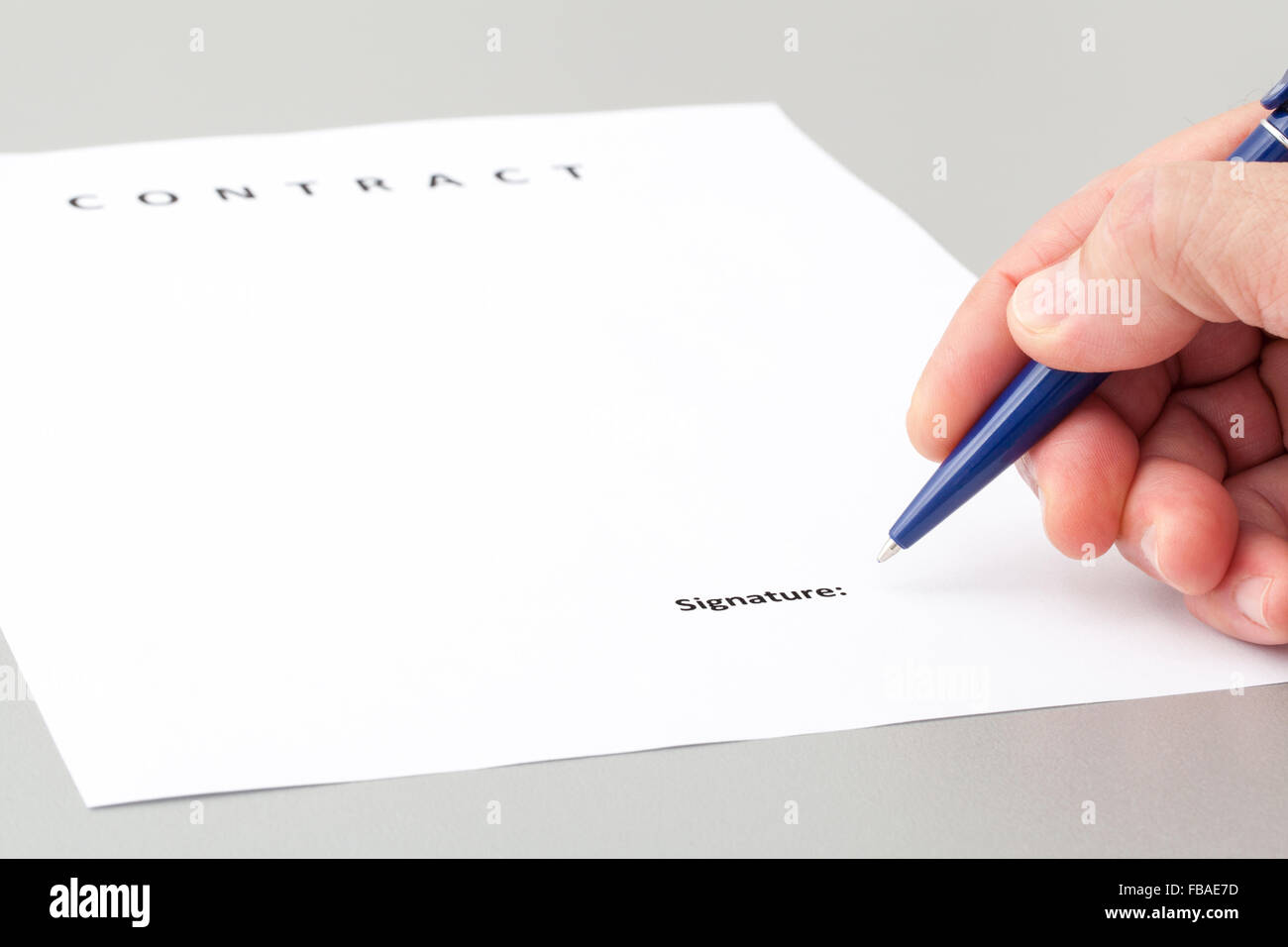 Man with a pen, signing a contract on a grey table in the office. - Stock Image