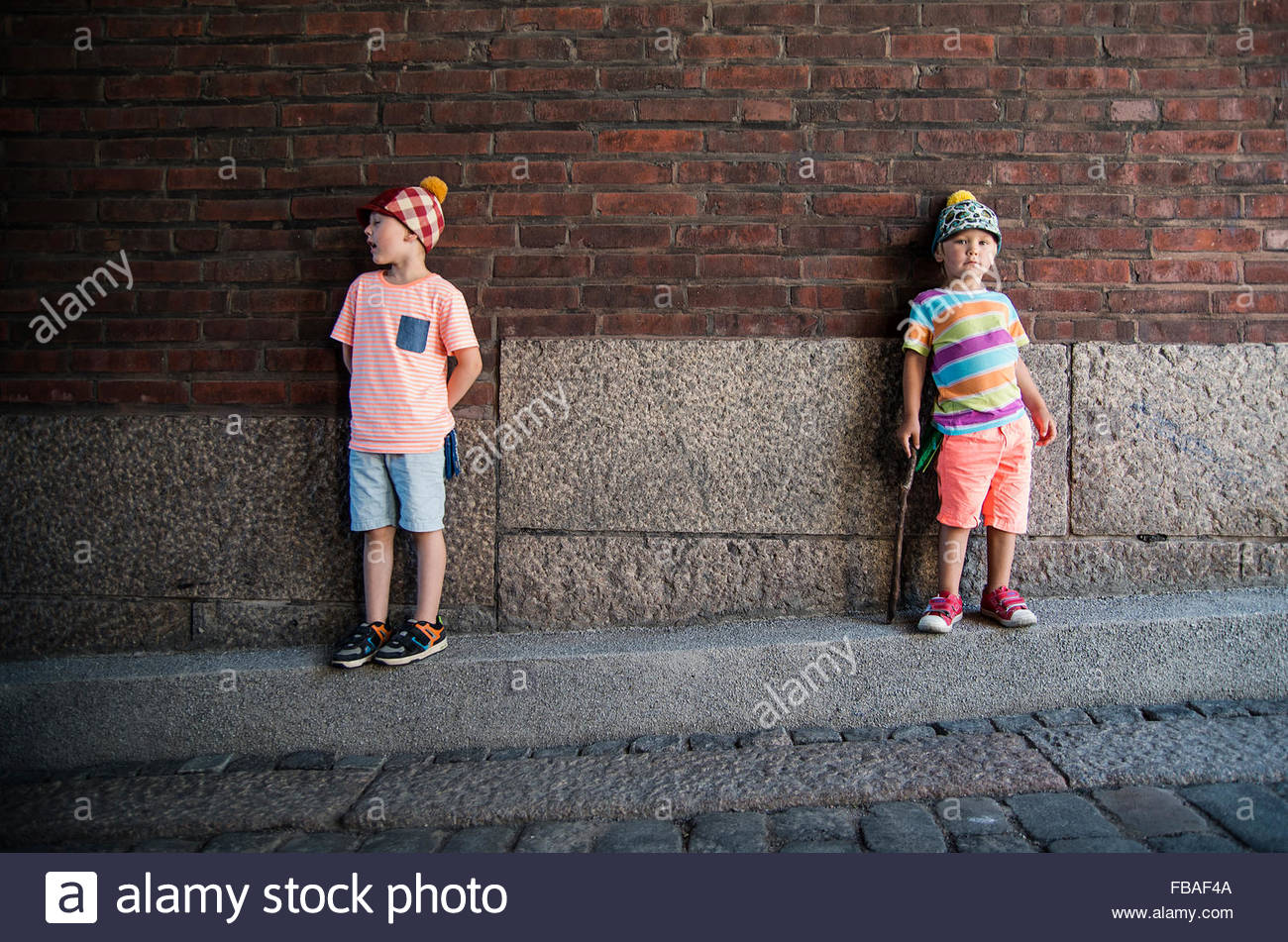 Finland, Helsinki, Boys (4-5) standing against brick wall - Stock Image