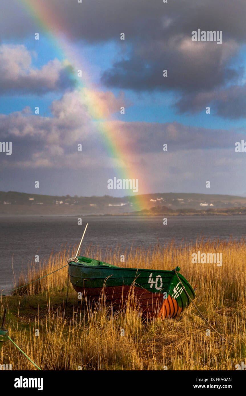 Wooden fishing boat and rainbow in Ardara, County Donegal, Ireland - Stock Image