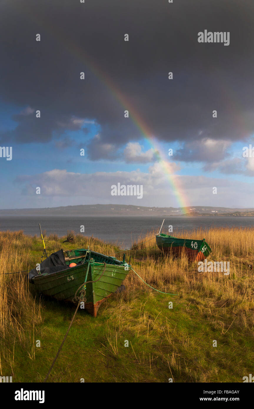 Wooden fishing boats and rainbow in Ardara, County Donegal, Ireland - Stock Image