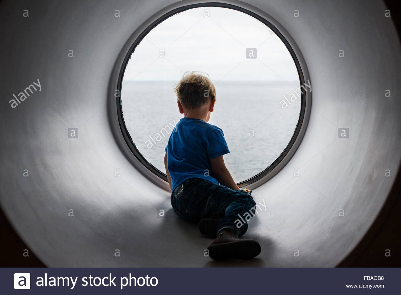 Back view of boy (4-5) looking through window at Baltic Sea - Stock Image