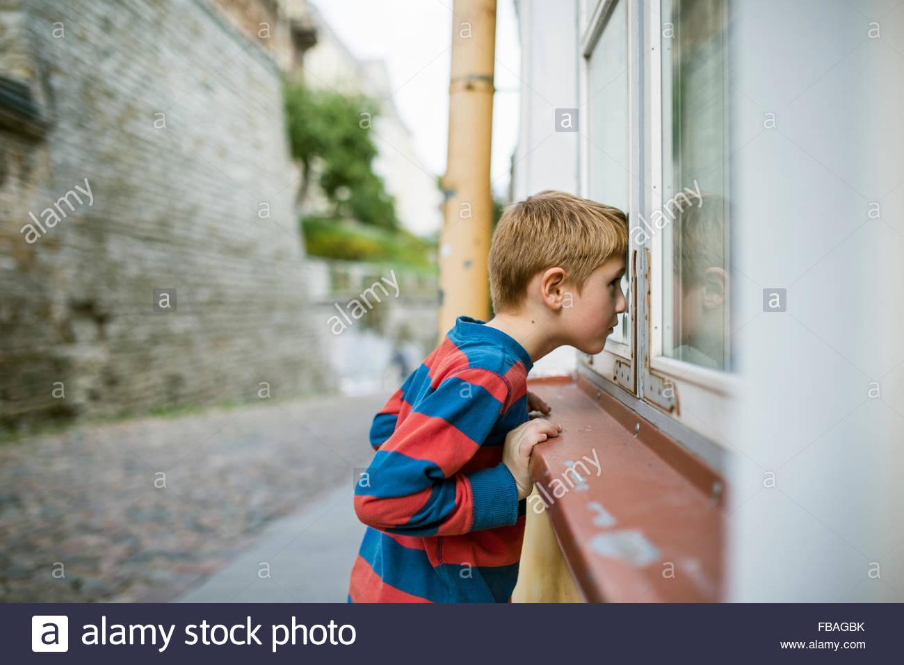 Estonia, Tallinn, Boy (6-7) looking into house through window - Stock Image
