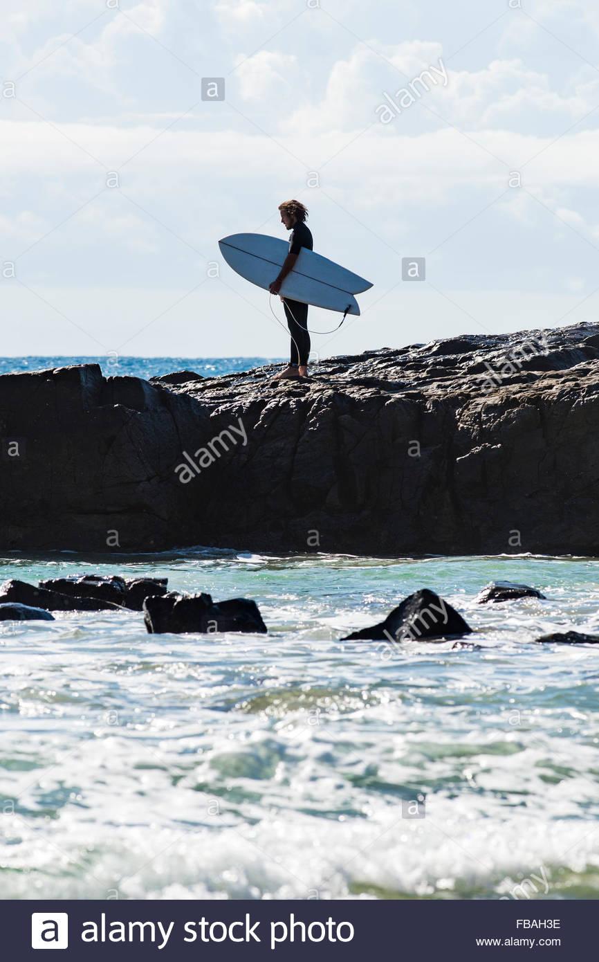 Australia, Queensland, Sunshine Coast, Noosa, Alexandria Bay, Young man holding surfboard on beach - Stock Image