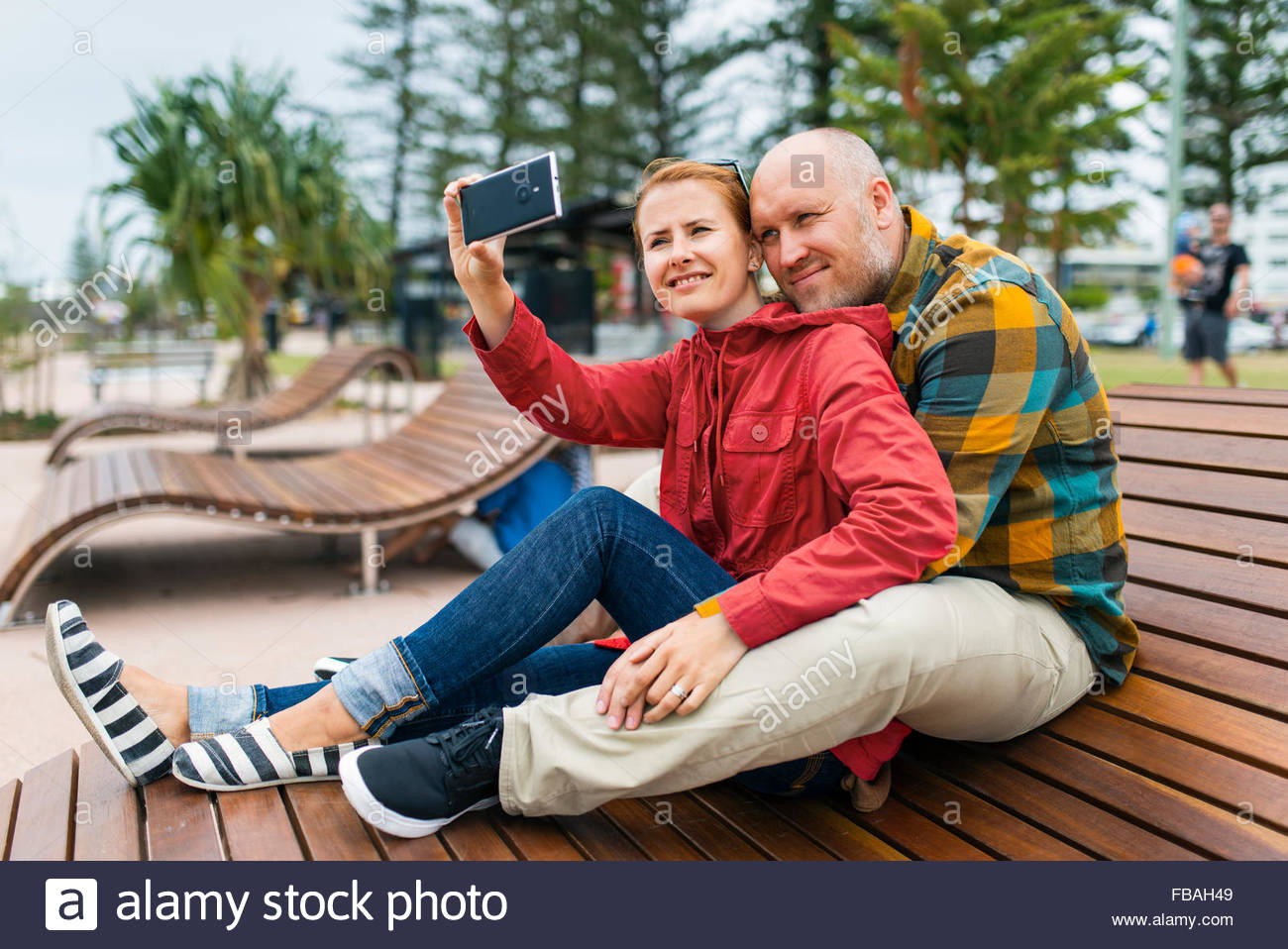 Australia, Queensland, Mid-adult couple taking selfie on bench in park - Stock Image