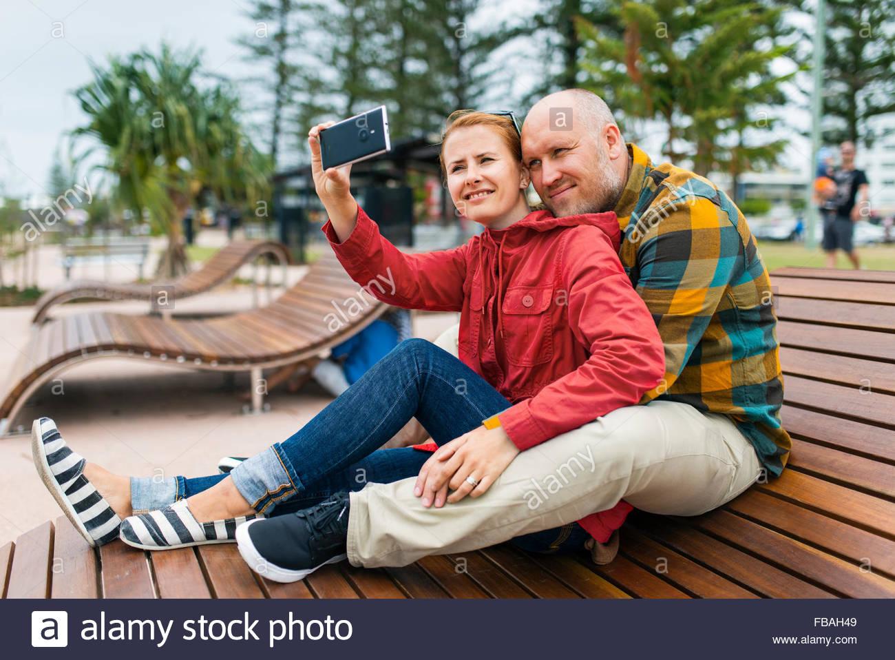 Australia, Queensland, Mid-adult couple taking selfie on bench in park Stock Photo