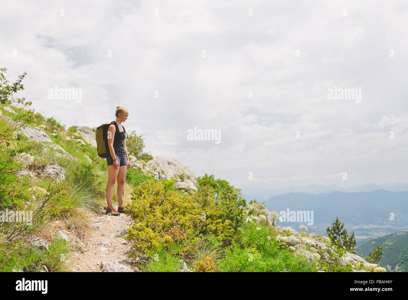 France, Pelleautier, Ceuse, Woman standing on hiking path on mountain side - Stock Image