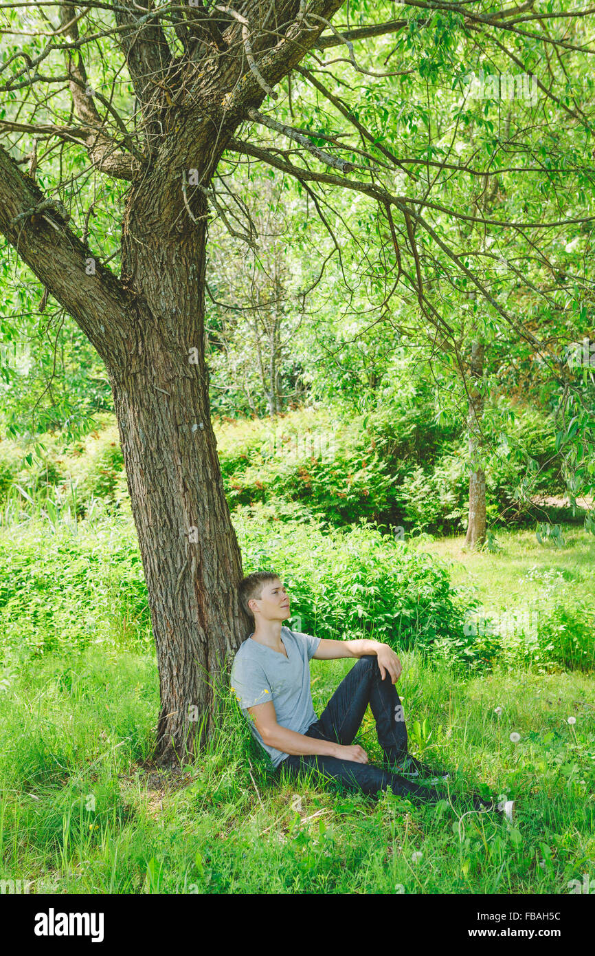 Finland, Helsinki, Aggelby, Young man sitting under dry tree - Stock Image