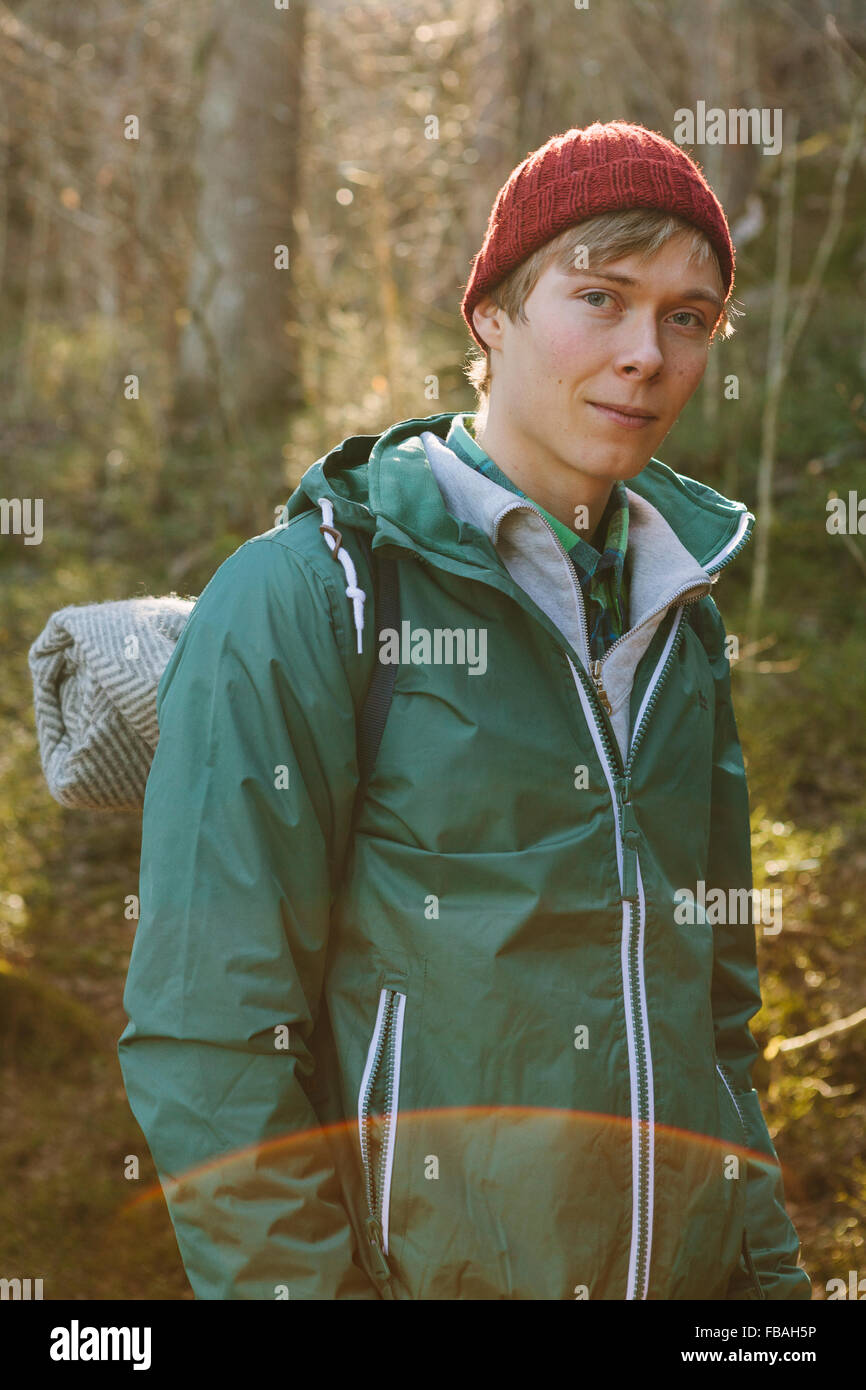 Finland, Esbo, Kvarntrask, Portrait of young man wearing woolly hat and windcheater jacket in forest - Stock Image