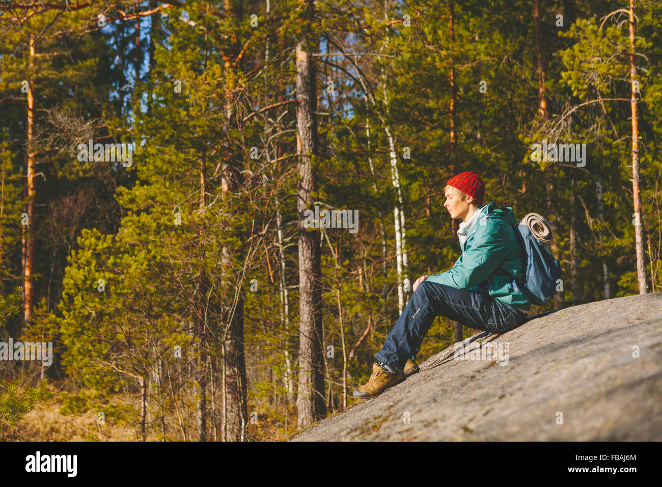 Finland, Esbo, Kvarntrask, Young man sitting on stone surface in forest - Stock Image