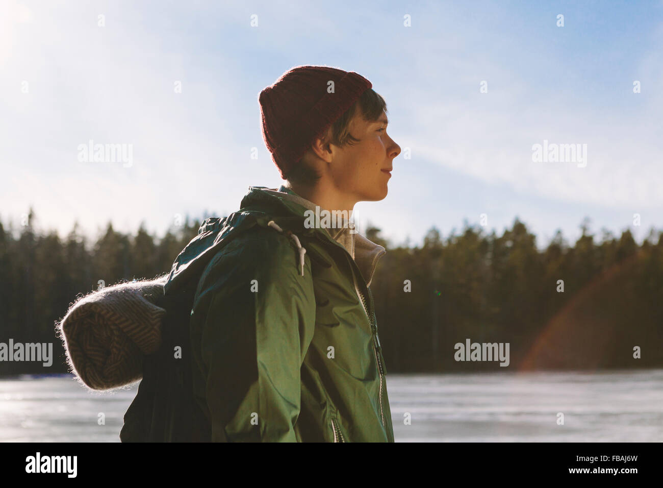 Finland, Esbo, Kvarntrask, Portrait of young man on shore of forest lake - Stock Image