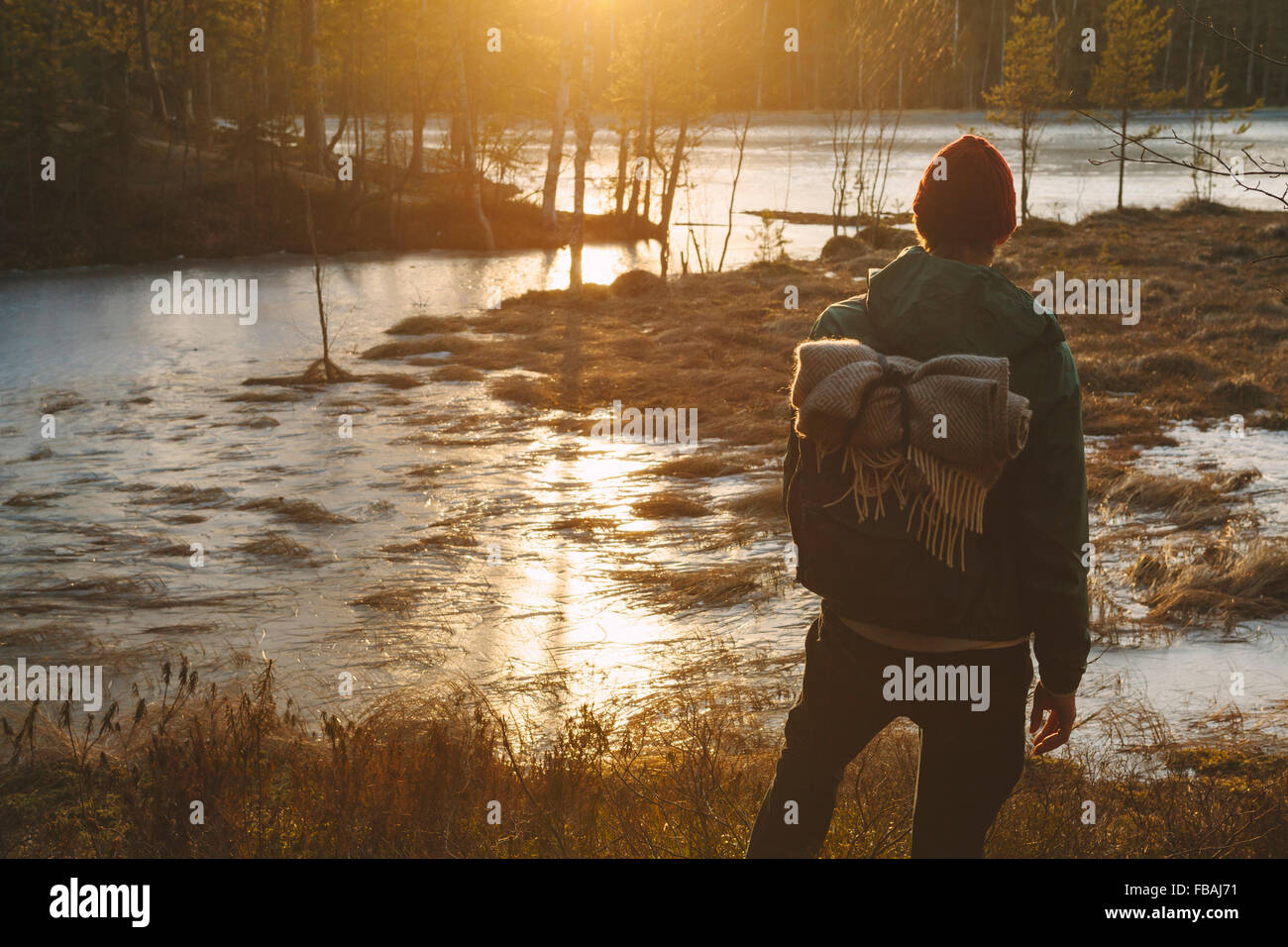 Finland, Esbo, Kvarntrask, Young man standing on marshy lakeshore Stock Photo