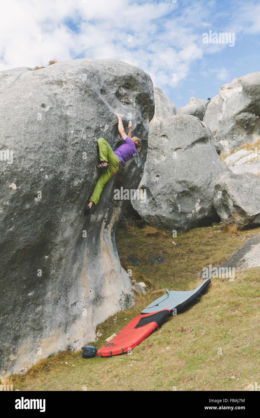 New Zealand, Castle Hill, Young man climbing up boulder with two crash pads prepared underneath - Stock Image