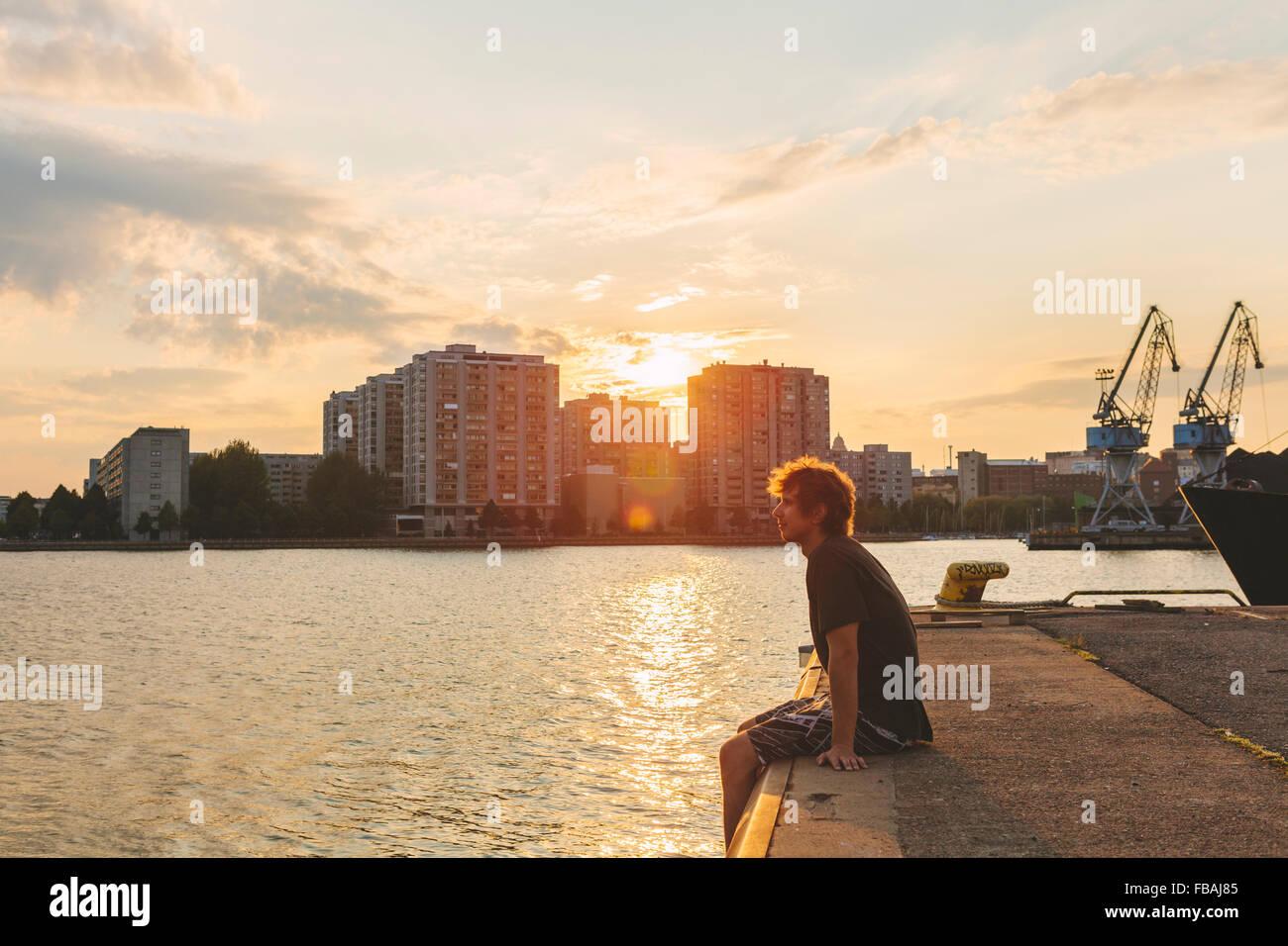 Finland, Helsinki, Uusimaa, Sompasaari, Man sitting on pier at sunset - Stock Image