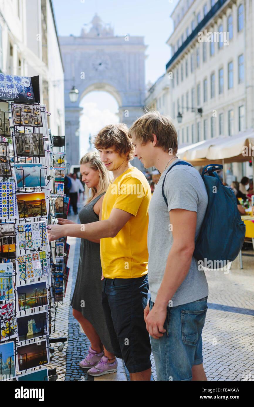 Portugal, Lisbon, Three tourists choosing postcards - Stock Image
