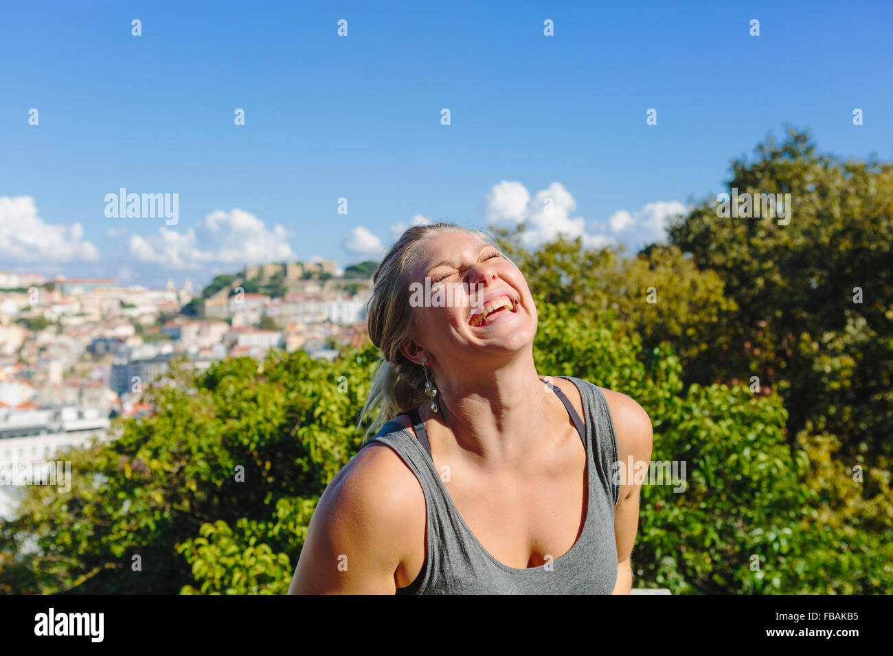 Portugal, Lisbon, Portrait of young woman laughing - Stock Image