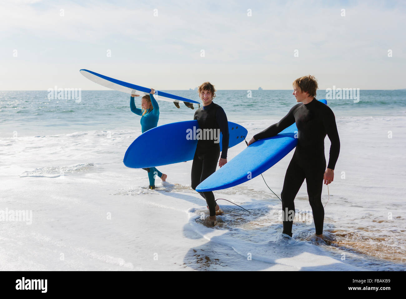 Portugal, Lisbon, Three people carrying surfboards on beach - Stock Image