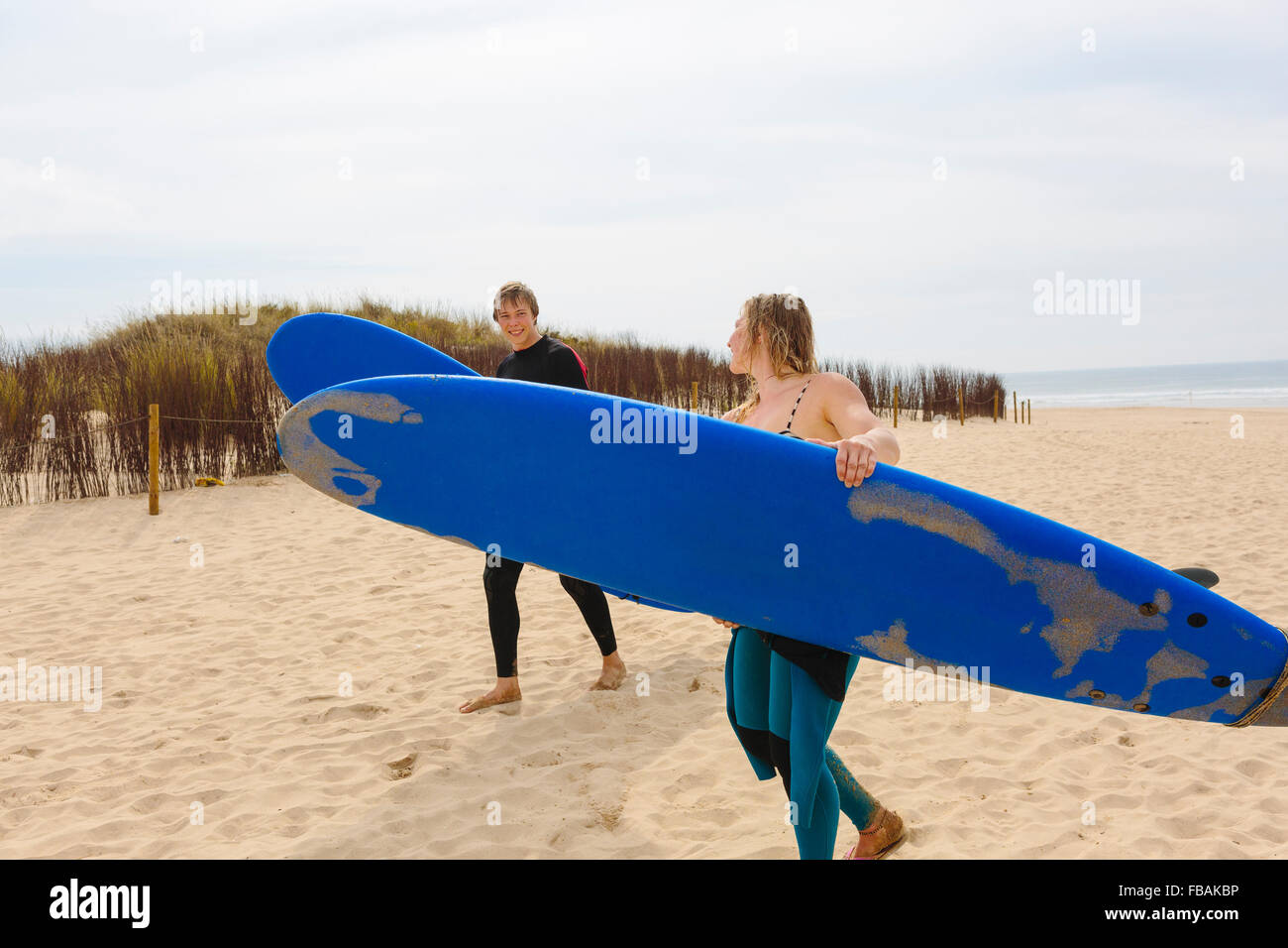 Portugal, Lisbon, Two people carrying surfboards on beach - Stock Image