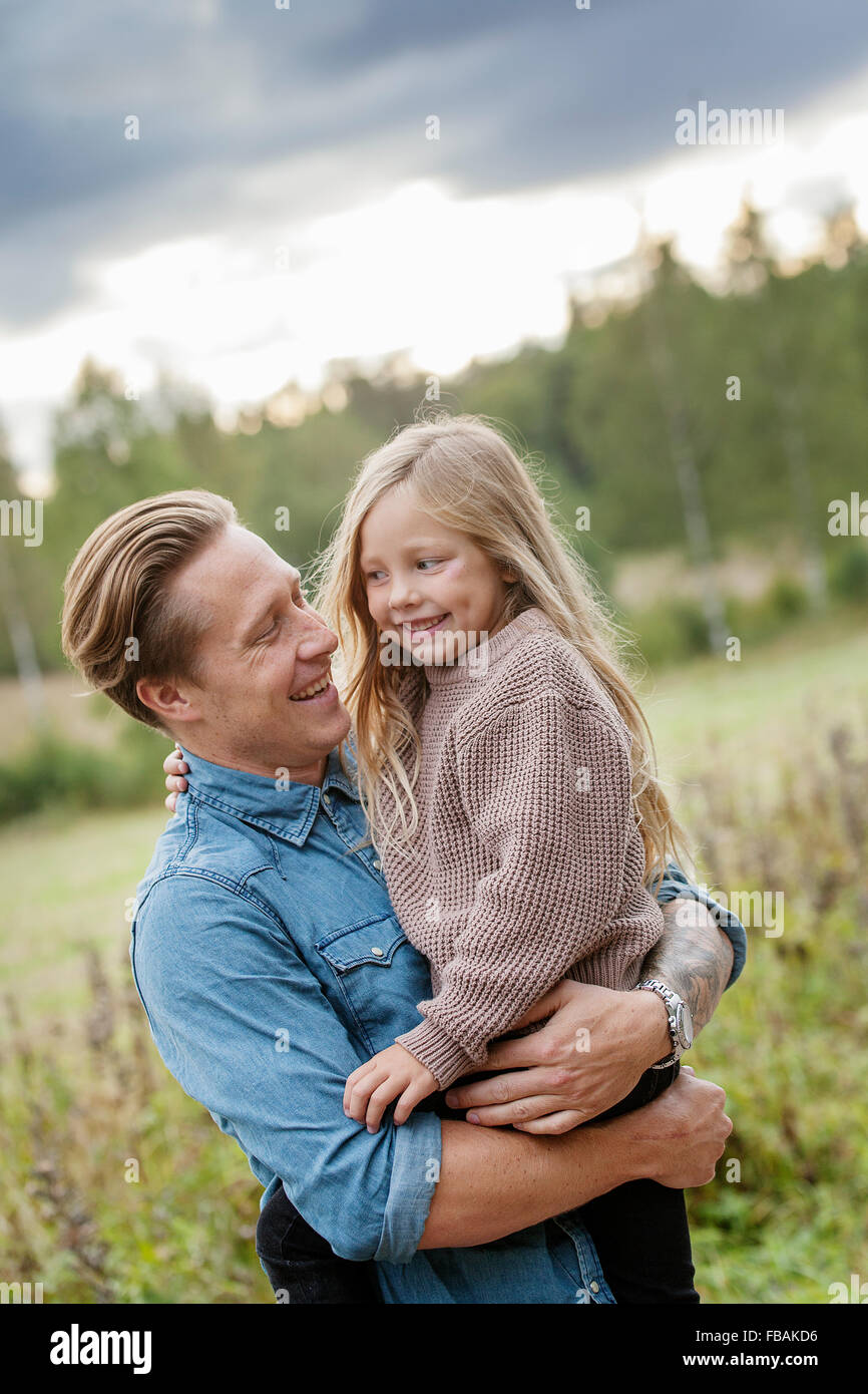 Finland, Uusimaa, Raasepori, Karjaa, Father holding his daughter (6-7) - Stock Image