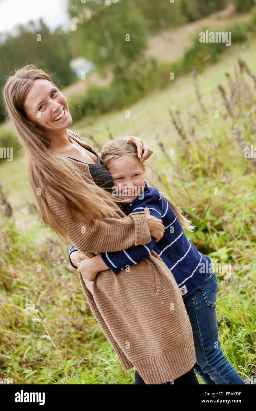 Finland, Uusimaa, Raasepori, Karjaa, Mother hugging her daughter (6-7) - Stock Image