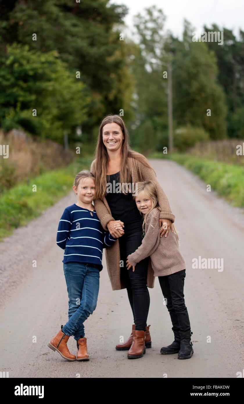 Finland, Uusimaa, Raasepori, Karjaa, Outdoor portrait of mother with two daughters (6-7) - Stock Image