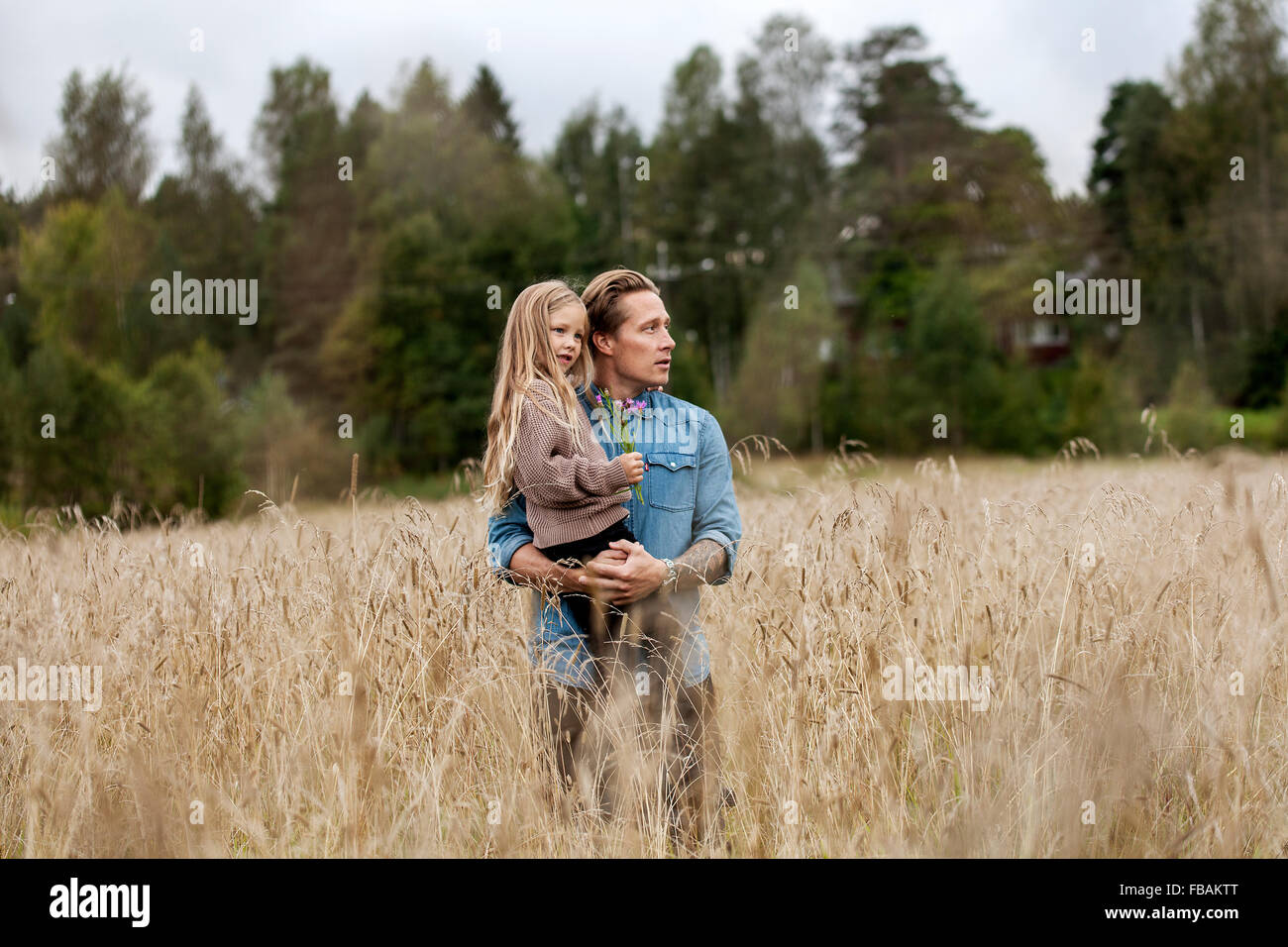 Finland, Uusimaa, Raasepori, Karjaa, Father with his daughter (6-7) looking at view - Stock Image