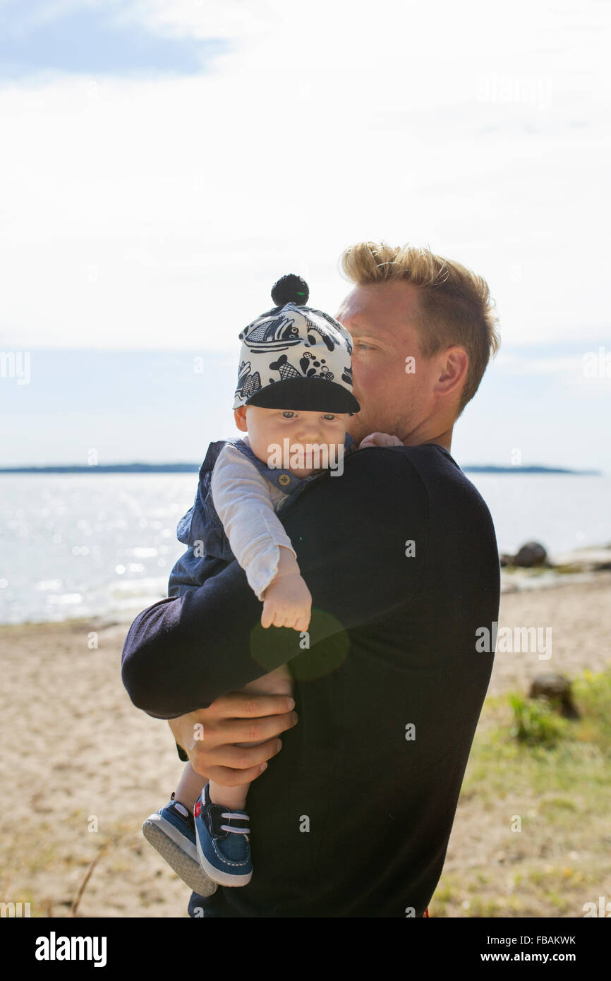 Finland, Uusimaa, Young father holding son (0-1 months) on beach - Stock Image