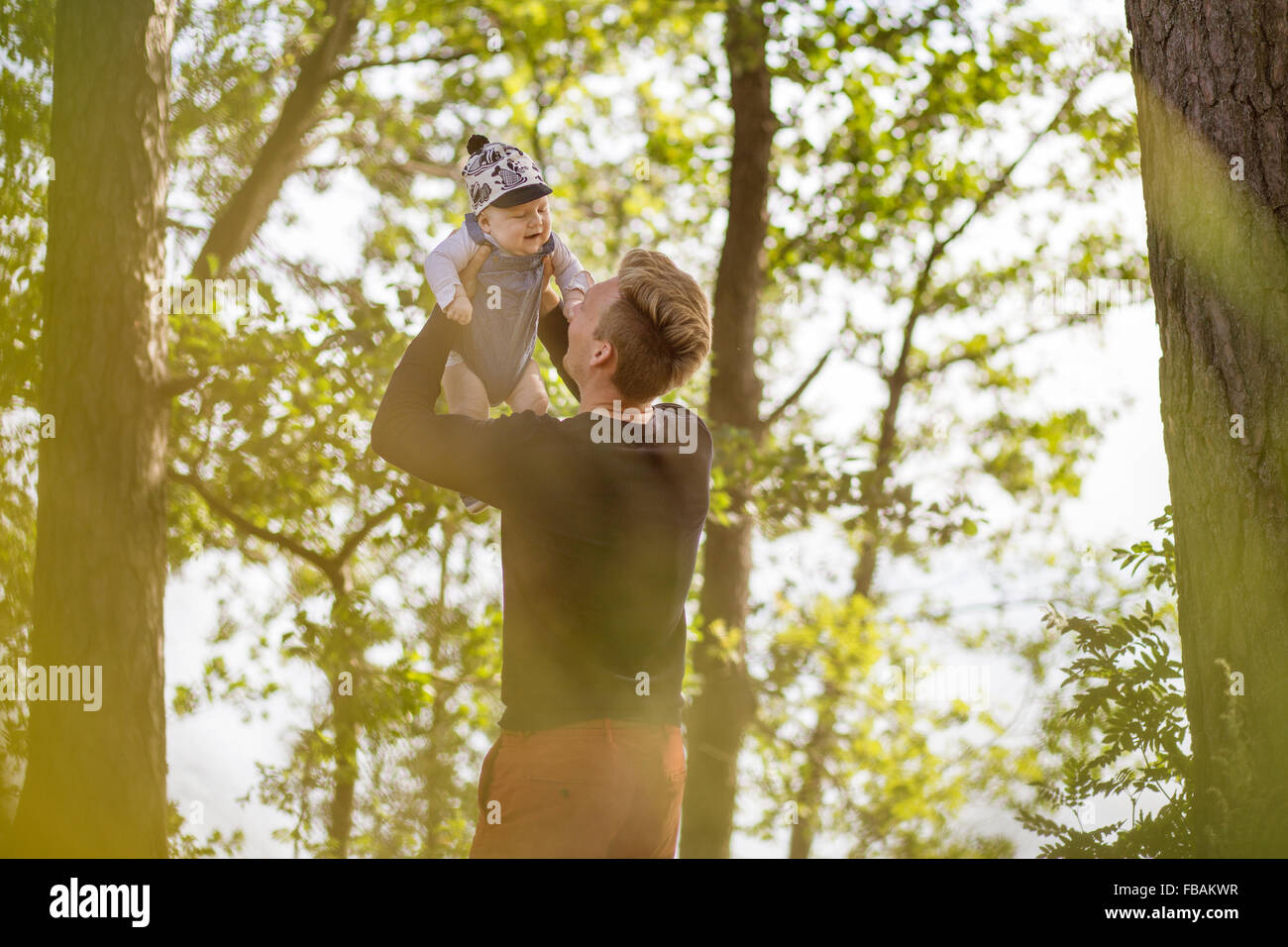 Finland, Uusimaa, Father lifting son (0-1 months) in air - Stock Image