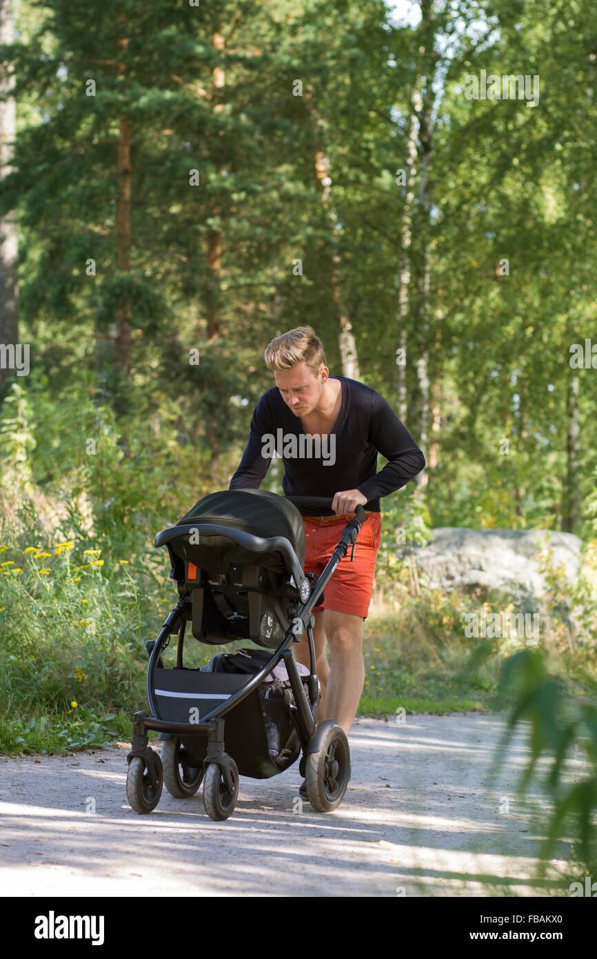 Finland, Uusimaa, Father walking with baby boy (0-1 months) in stroller - Stock Image