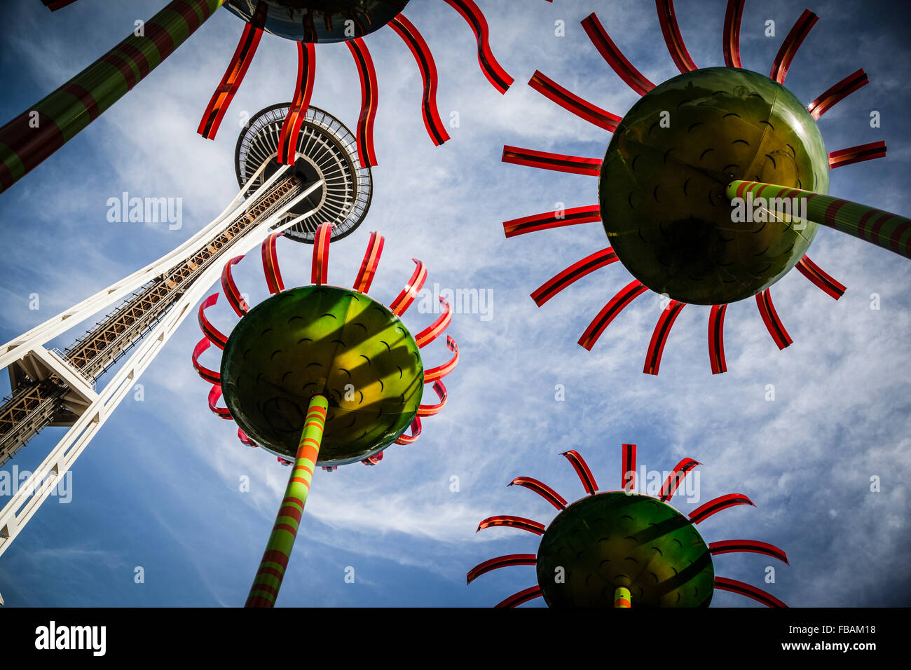The landmark Space Needle soars overhead with two colorful flower sculptures. - Stock Image