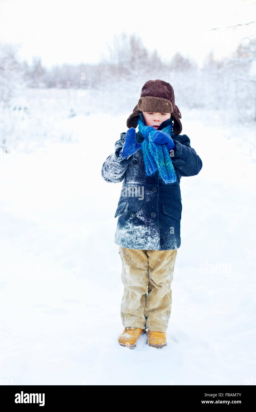 Finland, Keski-Suomi, Aanekoski, Young boy (6-7) standing in snowy meadow and adjusting scarf - Stock Image