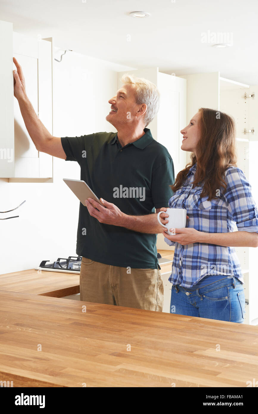 Woman With Carpenter Inspecting New Fitted Kitchen - Stock Image