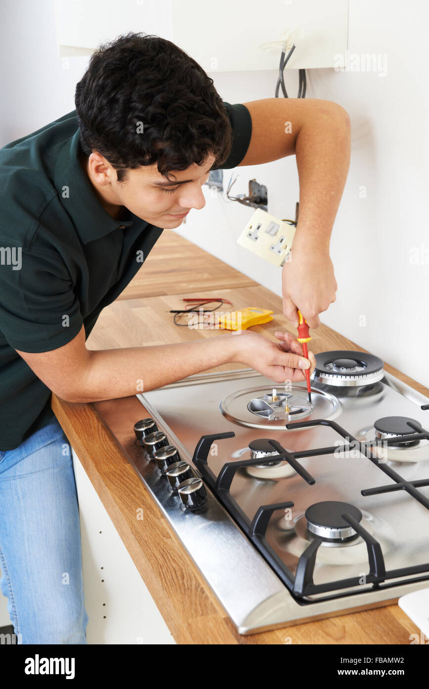 Workman Installing Gas Cooker In New Kitchen - Stock Image