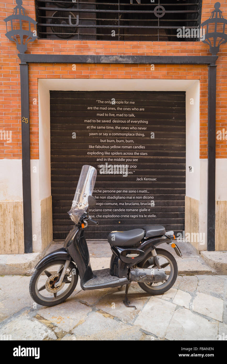 Scooter street Italy, view of a scooter parked in front of shutters bearing a text by Jack Kerouac, Marsala, Sicily. - Stock Image