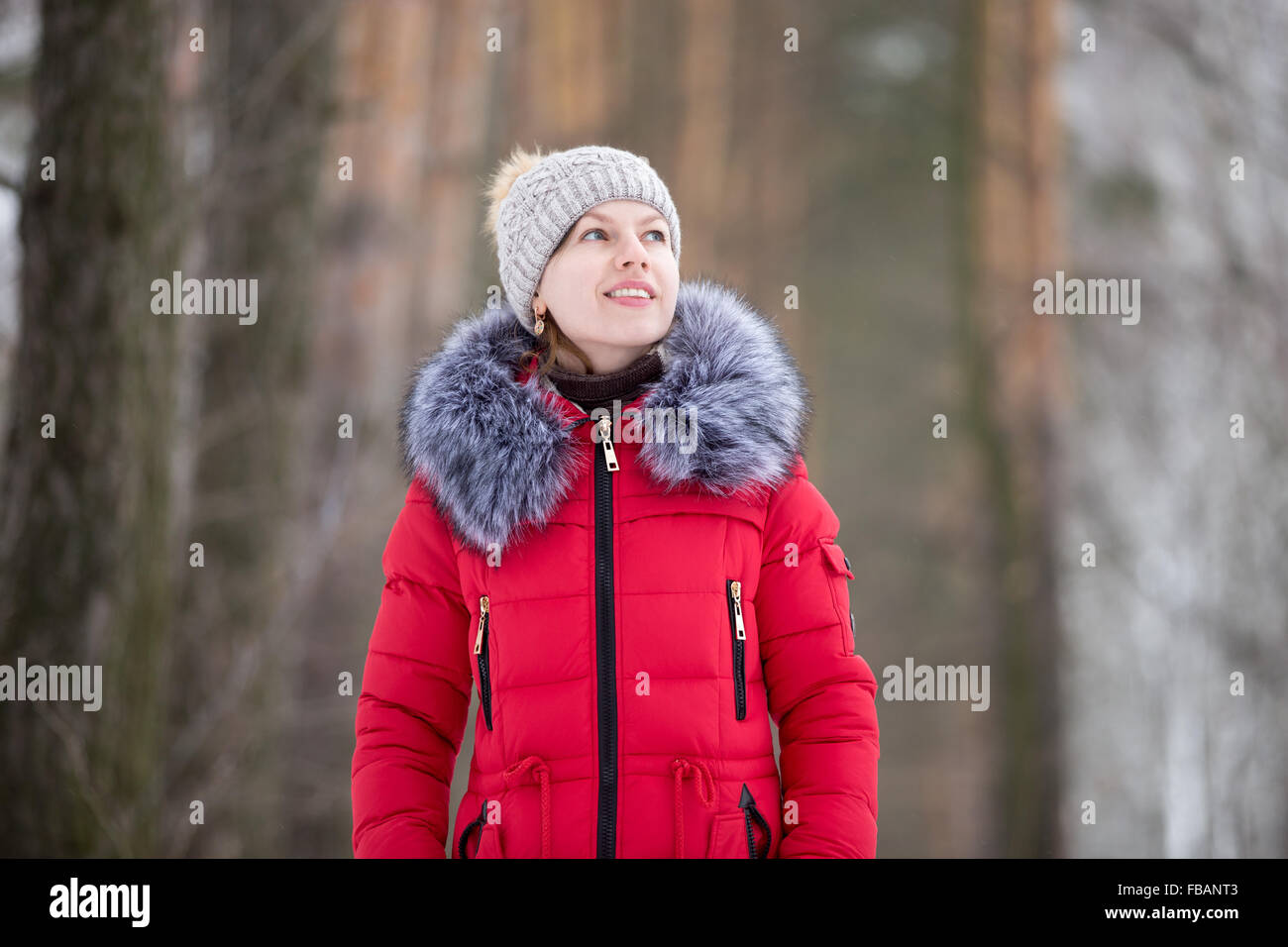 Beautiful girl in knitted hat and red winter coat with fur collar smiling dreamily outdoors - Stock Image