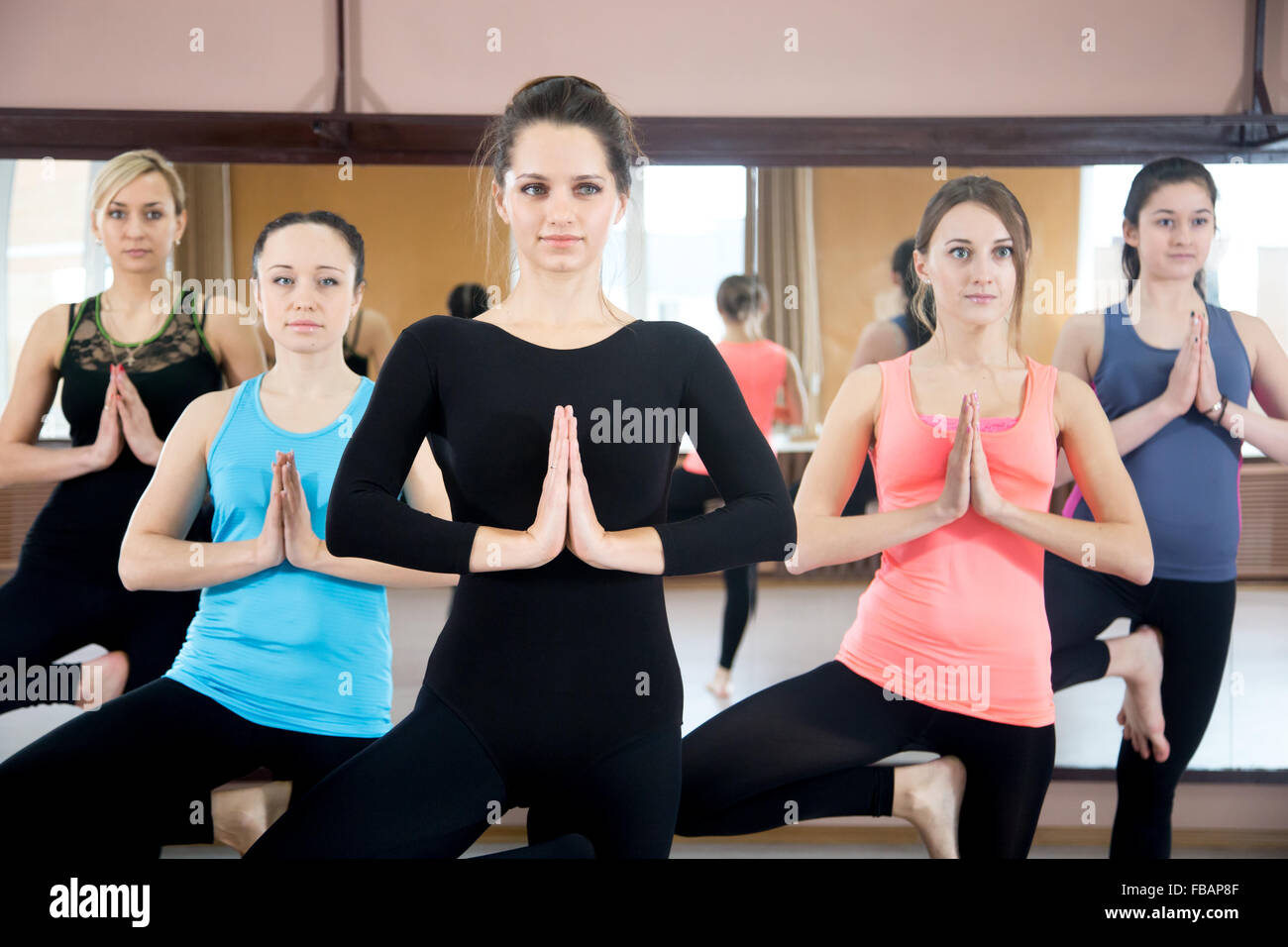 Sporty yogi girls in class in Yoga pose vrikshasana (Vriksasana or Tree Pose) using namaste - Stock Image
