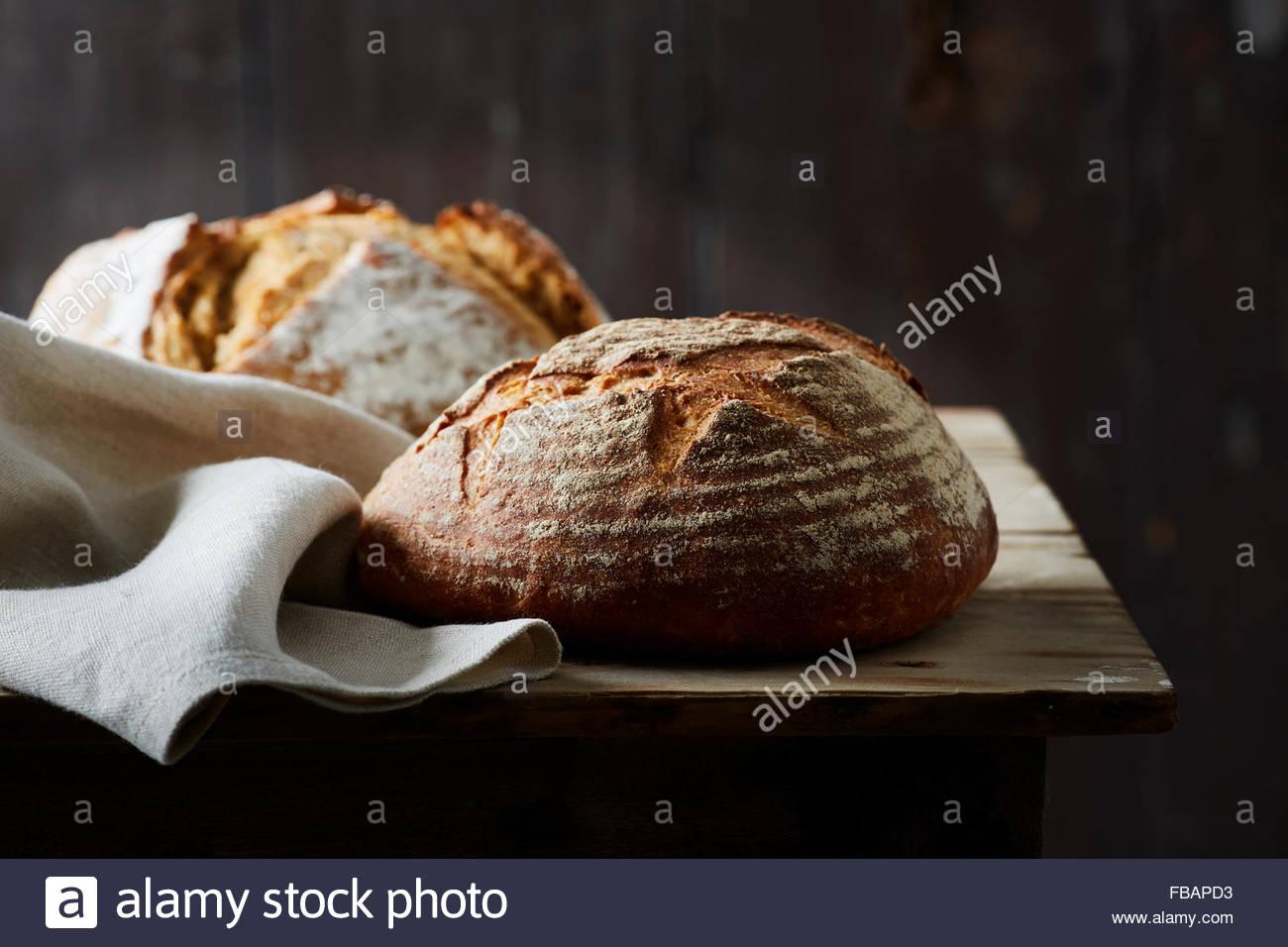artisan baked bread on dark background - Stock Image