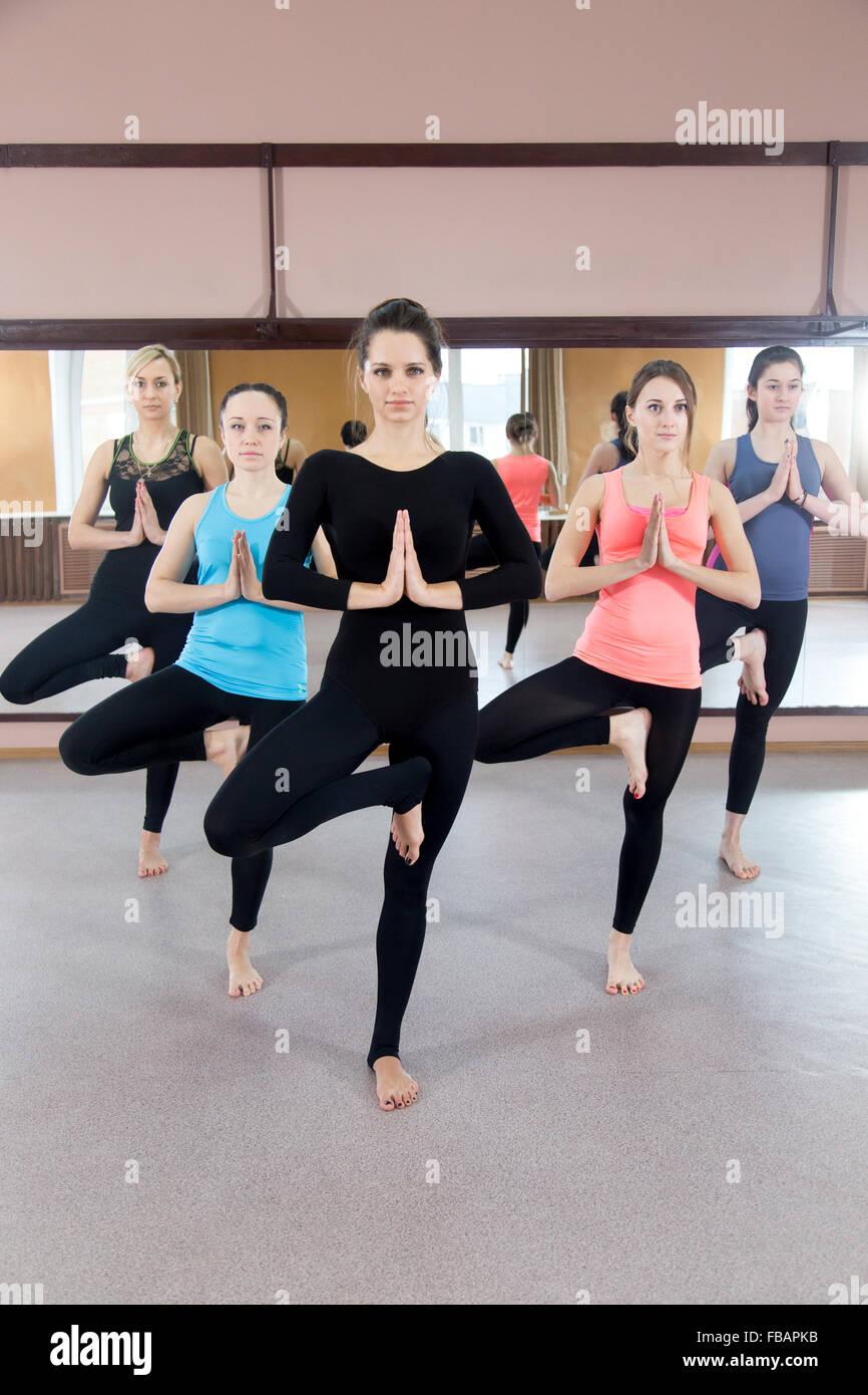 Sporty yogi girls in class in Yoga pose vrikshasana (Vriksasana or Tree Pose) using Namaste (full length) - Stock Image