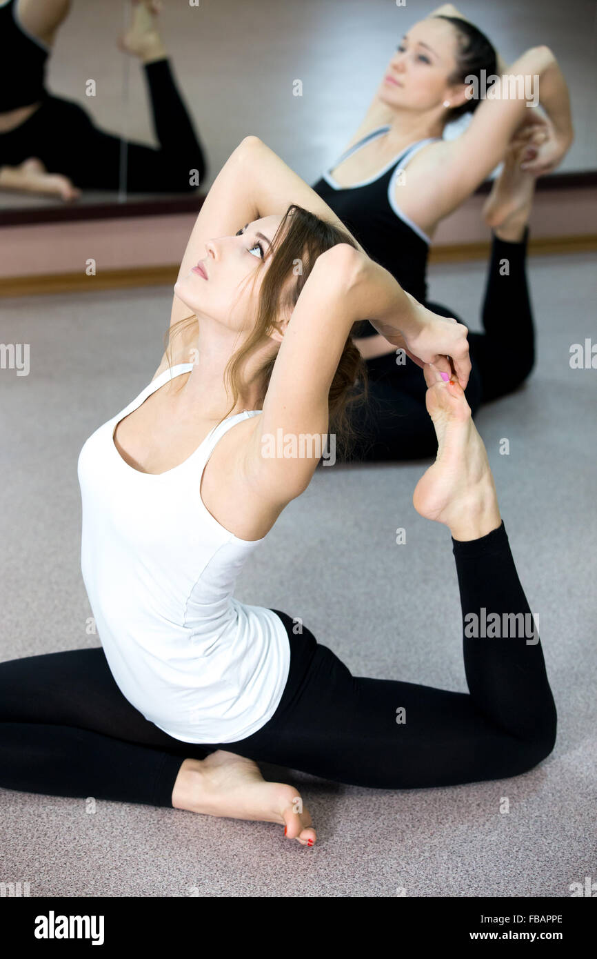 Sporty Yogi Girls doing yoga exercises backbends in class, sitting in asana eka pada radzhakapotasana (One-Legged - Stock Image