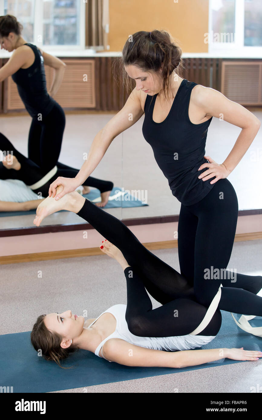 Yogatheraphy. Beautiful young females practicing yoga therapy, doing exercises in class, instructor assists to yogi - Stock Image